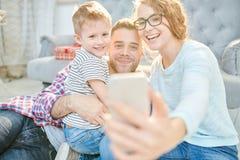 Família moderna que toma Selfie em casa foto de stock royalty free