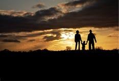 Família mostrada em silhueta no por do sol Fotografia de Stock Royalty Free