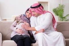 A família muçulmana árabe nova com a esposa grávida que espera o bebê imagem de stock royalty free