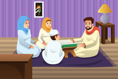 Família muçulmana que estuda o Corão em casa Imagens de Stock