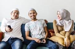 Família muçulmana que olha a tevê em casa imagens de stock