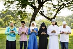 Família muçulmana que usa smartphones no parque imagens de stock royalty free