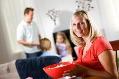 Família: A mulher feliz guarda a bacia grande de pipoca antes da noite de cinema Fotografia de Stock Royalty Free