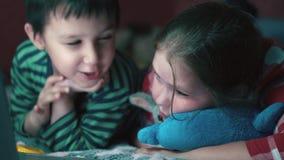 família Multi-étnica Irmã e irmão que encontram-se na cama que olha um filme no close-up 4K da tabuleta do portátil video estoque