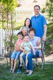 Família multi-étnico caucasiano chinesa que senta-se no banco foto de stock
