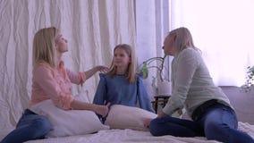 Família, mum feliz e filhas abraçando-se e para comunicar-se em casa na cama filme