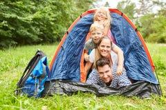 Família na barraca ao acampar em férias fotografia de stock