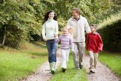Família na caminhada através do campo Fotos de Stock Royalty Free