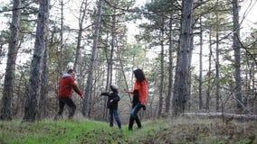 Família na caminhada da floresta do outono uma família feliz de três pessoas filme