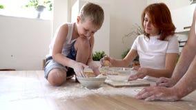 A família na cozinha joga a dispersão da farinha para cozinhar, movimento lento video estoque