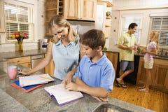 Família na cozinha que faz trabalhos de casa. fotos de stock royalty free