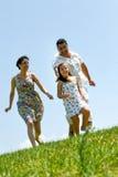 Família na erva sob o céu azul Imagem de Stock