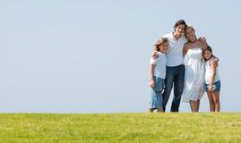Família na erva sob o céu azul imagens de stock