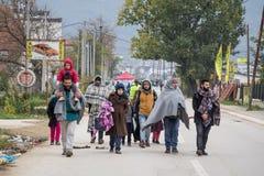 Família na frente de uma multidão de refugiados em sua maneira de registrar e entrar na Sérvia na beira com Macedônia na rota de  imagens de stock royalty free
