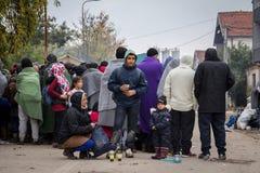 Família na frente de uma multidão de refugiados que esperam para registrar e entrar na Sérvia na beira com Macedônia na rota de B fotografia de stock royalty free