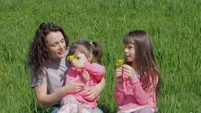 A família na grama verde está aspirando flores A mamã e a filha estão sentando-se no gramado Mulher com as meninas na natureza de video estoque