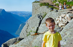 Família na parte superior maciça do penhasco de Preikestolen (Noruega) Imagens de Stock Royalty Free