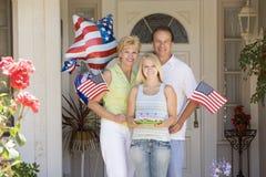 Família na porta da rua no quarto de julho com bandeiras Fotografia de Stock Royalty Free