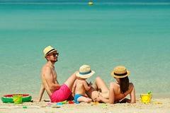 Família na praia Criança que joga com mãe e pai fotografia de stock royalty free