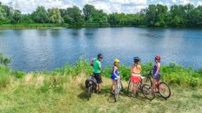 Família nas bicicletas que dão um ciclo fora, em pais e em crianças ativos nas bicicletas, opinião aérea a família feliz com as c foto de stock