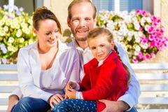 Família no banco do jardim na frente da casa Fotos de Stock Royalty Free