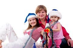 Família no chapéu de Santa que senta-se na neve artificial Fotografia de Stock