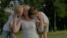 Família no dia ensolarado do verão no parque Crianças que jogam com seus pais vídeos de arquivo