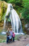Família no fundo da cachoeira do verão imagem de stock