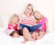 Família no livro de leitura da cama Fotografia de Stock