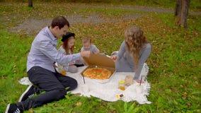 Família no parque do outono que come a pizza no gramado video estoque