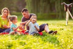 A família no parque - espuma da sopa do sopro da criança masculina e faz bolhas no na imagens de stock
