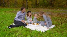A família no parque na queda, come no gramado video estoque