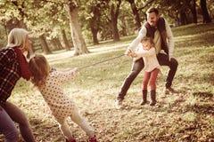 Família no parque que joga e que aperta a corda foto de stock royalty free