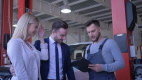 A família no serviço do carro, consumidores novos dos pares consulta com o técnico sobre a auto manutenção e dá chaves para o veí video estoque