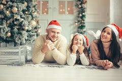 Família nos chapéus de Santa do Natal que encontram-se na cama Pai e bebê da mãe que têm o divertimento fotografia de stock