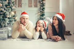 Família nos chapéus de Santa do Natal que encontram-se na cama Pai e bebê da mãe que têm o divertimento foto de stock royalty free