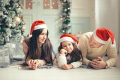 Família nos chapéus de Santa do Natal que encontram-se na cama Pai e bebê da mãe que têm o divertimento fotos de stock royalty free