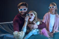 Família nos vidros 3d que sentam-se no sofá e que comem a pipoca Fotos de Stock Royalty Free