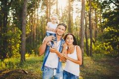 Família nova à moda do louro do bebê de um ano da mamã, do paizinho e da filha que senta-se perto do pai em ombros, fora fora da  imagens de stock