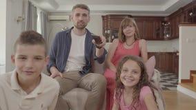 Família nova alegre do retrato que olha a tevê ao sentar-se em casa junto O pai guarda o telecontrole e comuta filme