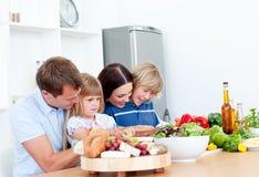 Família nova alegre que cozinha junto fotografia de stock