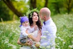 a família nova anda com as crianças no parque bonito em um por do sol, cordialmente abraço e o sorriso, mãe na cabeça tem uma gri imagem de stock royalty free