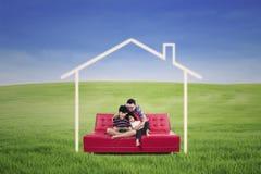 Família nova assentada em um sofá que sonha uma casa na natureza Fotografia de Stock Royalty Free