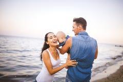 Família nova bonita em férias com bebê O pai guarda a menina loura em seus braços, e a mãe moreno do ` s abraça sua HU Imagem de Stock Royalty Free