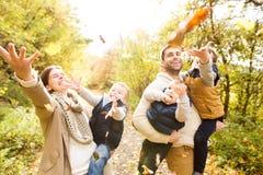 Família nova bonita em uma caminhada na floresta do outono Imagens de Stock