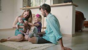 Família nova bonita: o mum, o paizinho, a filha pequena e o filho do bebê estão sentando-se no assoalho da cozinha Movimento lent video estoque