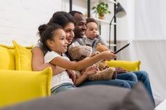 família nova bonita que olha a tevê junto imagens de stock royalty free