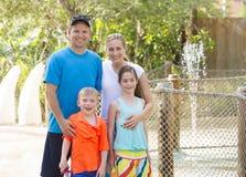 Família nova bonito que aprecia um dia em um parque de diversões do ar livre Fotografia de Stock