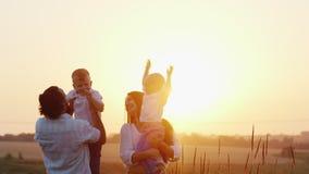 Família nova com as duas crianças que jogam na natureza No por do sol video estoque