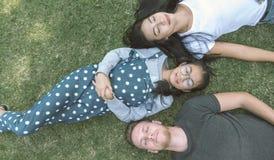 Família nova com a filha que coloca no parque na grama verde e que olha a câmera, vista superior fotografia de stock royalty free